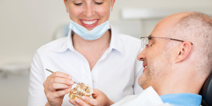 Smiling female dentist explaining artificial teeth to patient in clinic