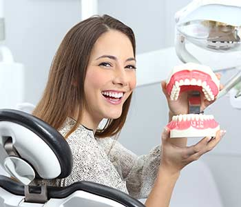 Young lady smiling with perfect teeth after whitening treatment and holding a plastic denture in a box